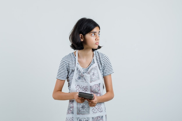 T- 셔츠, 앞치마에 계산기를 들고 집중 찾고 어린 소녀.