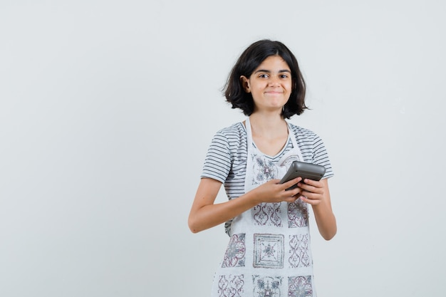 Little girl holding calculator in t-shirt, apron and looking cheerful.