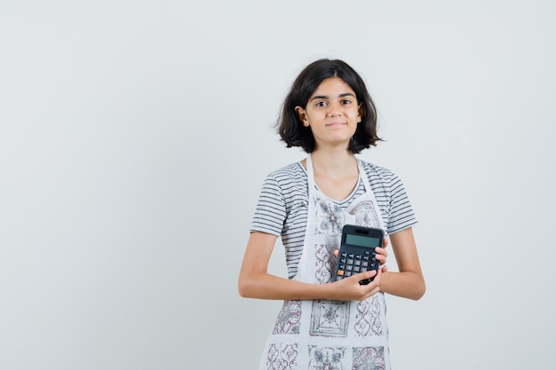 Little girl holding calculator in t-shirt, apron and looking confident ,
