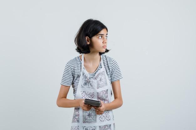 Bambina che tiene la calcolatrice in maglietta, grembiule e sguardo concentrato.