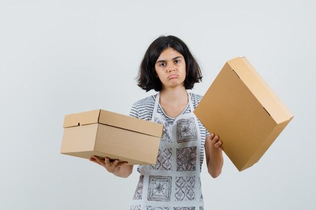 Bambina con scatole di cartone in t-shirt, grembiule e guardando confuso,