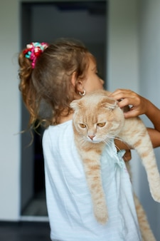 Little girl holding cat in her arms at home indoor, child playing with domestic animals pet, lovely friend.