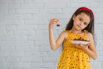 Little girl holding cherry and plate in front of white brick wall