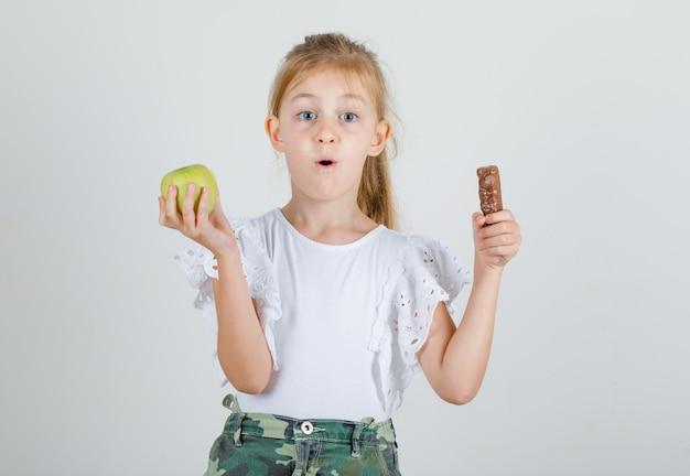 Маленькая девочка держит шоколад и зеленое яблоко в белой футболке
