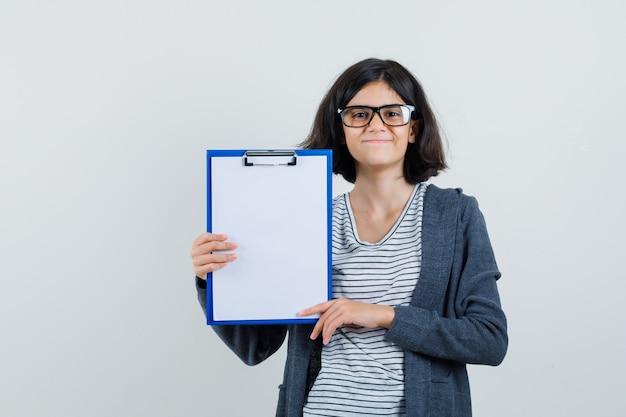 T- 셔츠, 재킷에 클립 보드를 들고와 쾌활 한 찾고 어린 소녀.