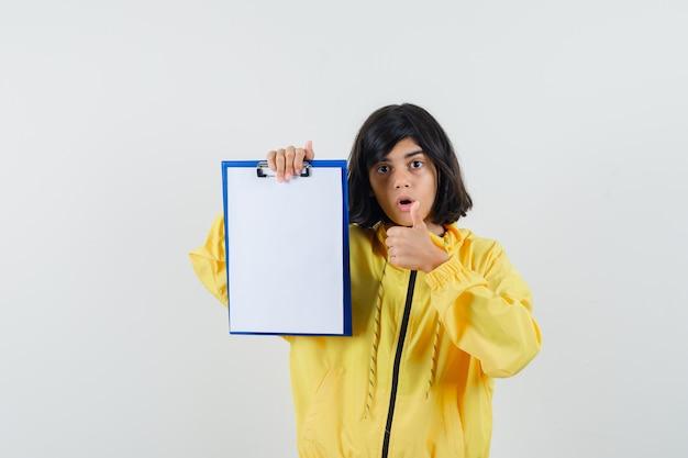Bambina che tiene appunti, mostrando il pollice in su in felpa con cappuccio gialla e guardando stupito. vista frontale.