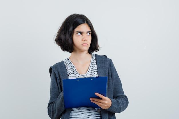 Bambina che tiene appunti in t-shirt, giacca e sguardo esitante.