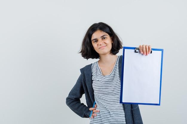 T- 셔츠, 재킷에 연필로 클립 보드를 들고 자신감을 찾고 어린 소녀.