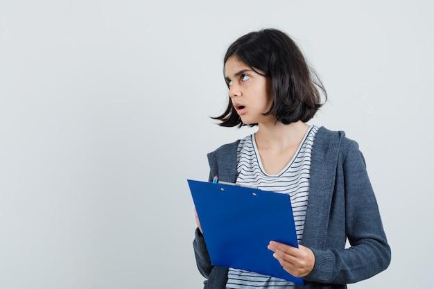 T- 셔츠, 재킷에 연필로 클립 보드를 들고 혼란 스 러 워 보이는 어린 소녀.