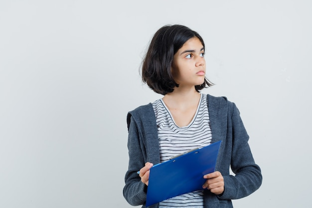 T- 셔츠, 재킷에 연필로 클립 보드를 들고와 초점을 찾고 어린 소녀.