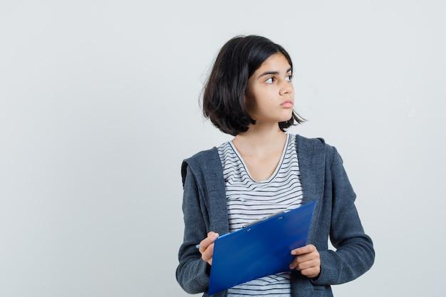 Tシャツ、ジャケット、焦点を合わせて鉛筆でクリップボードを保持している少女。