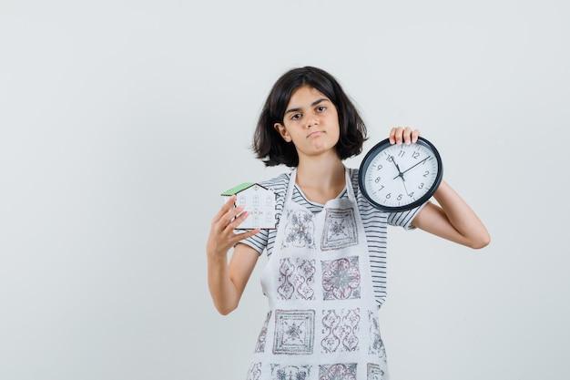 Маленькая девочка держит часы и модель дома в футболке, фартуке и задумчиво смотрит