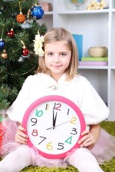 部屋のクリスマスツリーの近くで時計を保持している少女