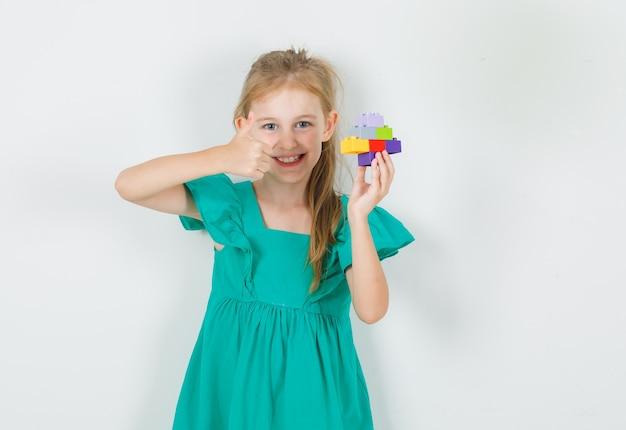 Bambina che tiene i blocchi variopinti del costruttore con il pollice in su in vestito verde e che sembra allegro. vista frontale.