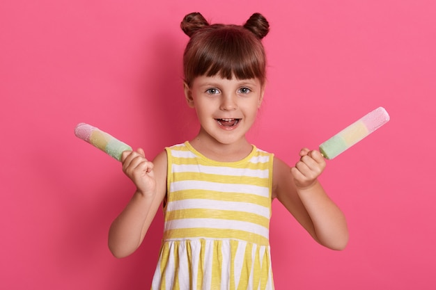 カラフルなアイスキャンデーを押し、興奮した表情、幸せそうな表情でポーズ、ピンクの壁に白と黄色の剥かれた夏のドレスを着ている少女。