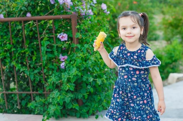 トウモロコシを押しながら春のドレスで庭でカメラ目線と幸せそうに見えて小さな女の子。正面図。