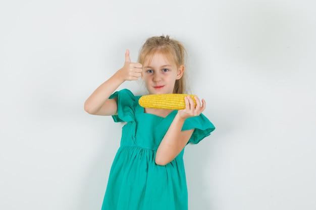 Маленькая девочка держит кукурузу и показывает палец вверх в зеленом платье и выглядит довольным. передний план.