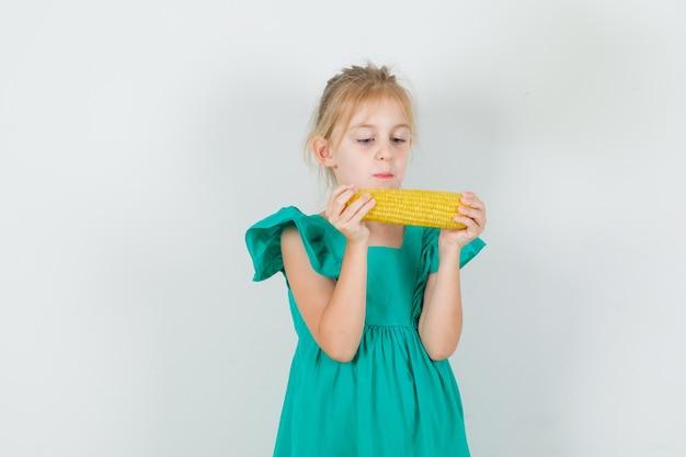 Маленькая девочка держит кукурузу в зеленом платье, вид спереди.