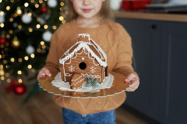 Маленькая девочка держит украшенный пряничный домик