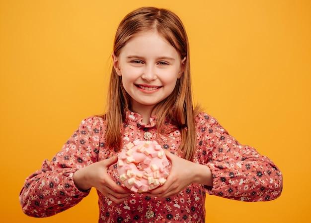 Маленькая девочка держит пончик и смотрит в камеру, изолированную на желтом фоне
