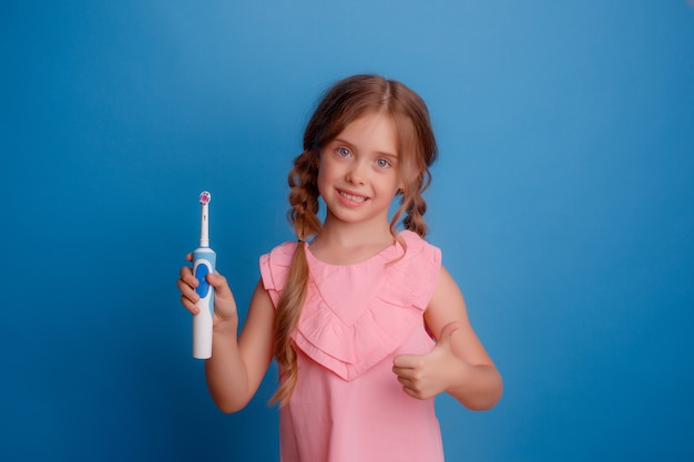 Little girl holding electric toothbrush