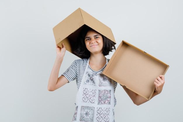 Tシャツ、エプロン、陽気に見える空の段ボール箱を保持している少女、