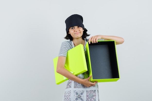 空のプレゼントボックスを持って、キッチンドレスで笑っている少女、