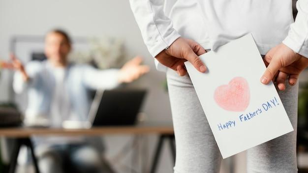 Маленькая девочка держит открытку на день отца как сюрприз для своего отца