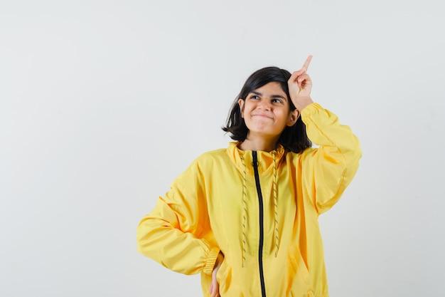 黄色いパーカーで頭上に指を持ち、夢のような正面図を探している少女。