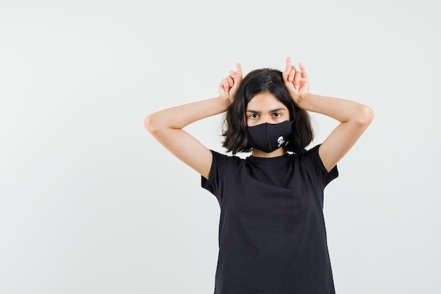 Little girl holding fingers over head as bull horns in black t-shirt, mask and looking funny , front view.