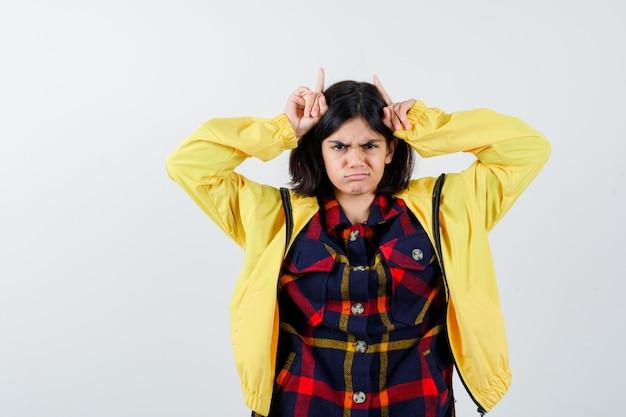 Bambina che tiene le dita sopra la testa come corna in camicia a quadri, giacca e sembra divertente