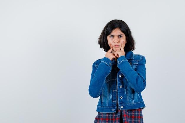 シャツ、ジャケットの頬に指を持って動揺している少女、正面図。