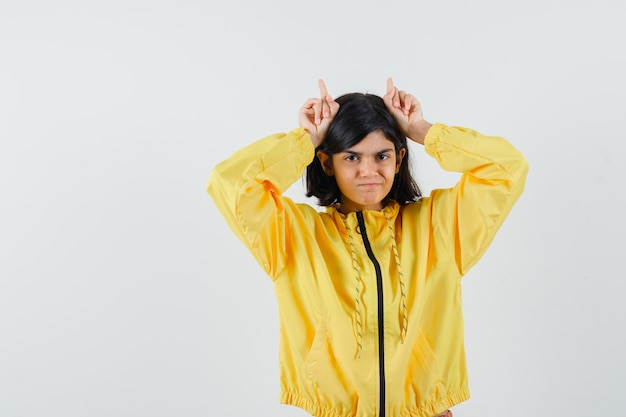 黄色いパーカーの雄牛の角のように頭の上に指を持って、面白い、正面図を探している少女。