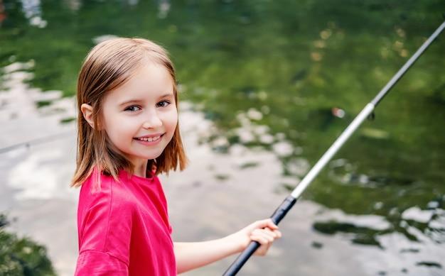 Маленькая девочка держит удочку на фоне пруда