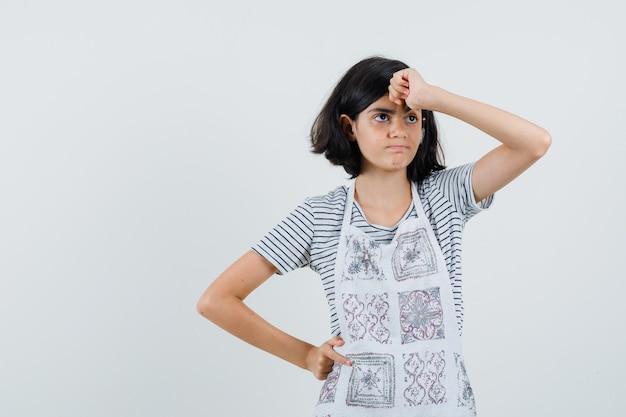 Маленькая девочка держит кулак на лбу в футболке, фартуке и извиняется,