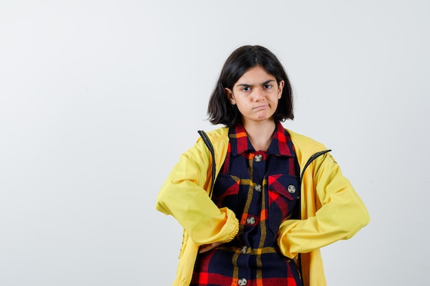 Little girl holding fists on stomach in checked shirt, jacket and looking confident , front view.
