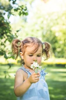 Little girl holding a flower outdoors.