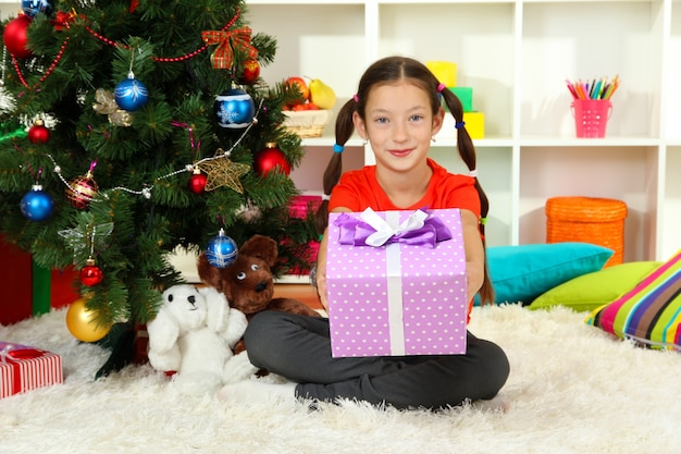 クリスマスツリーの近くにギフトボックスを保持している少女