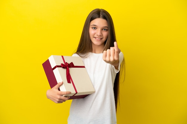 Little girl holding a gift over isolated yellow background doing coming gesture