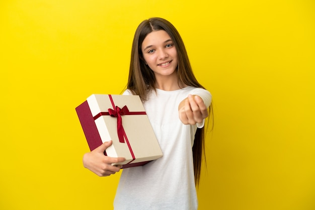 Little girl holding a gift over isolated yellow background making money gesture