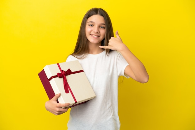 Little girl holding a gift over isolated yellow background making phone gesture. call me back sign