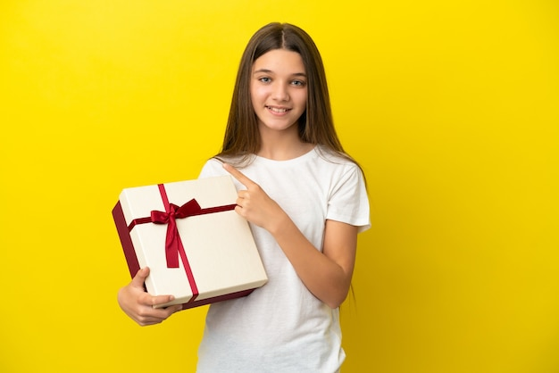 Little girl holding a gift over isolated yellow background pointing to the side to present a product