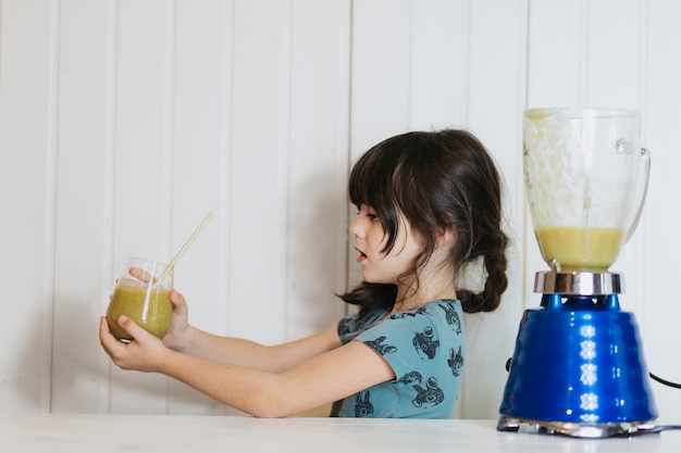 Little girl holding glass of smoothie
