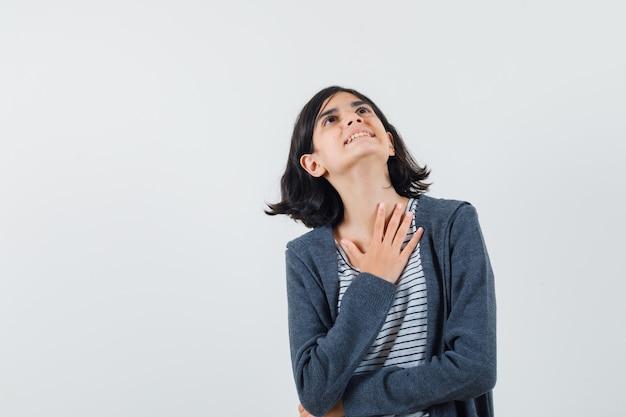Bambina che tiene la mano sul petto in t-shirt, giacca e sembra grata
