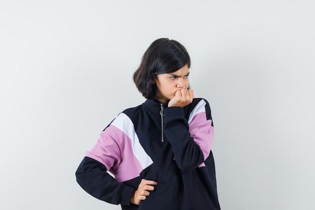 Bambina che tiene la mano sul mento in camicia e che sembra triste, vista frontale.