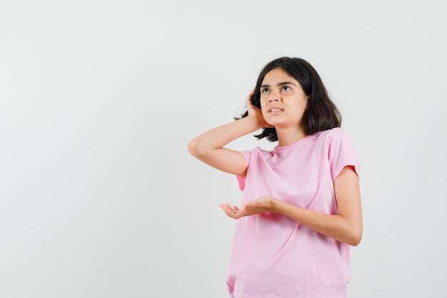Bambina che tiene la mano dietro l'orecchio in maglietta rosa e guardando curioso, vista frontale.
