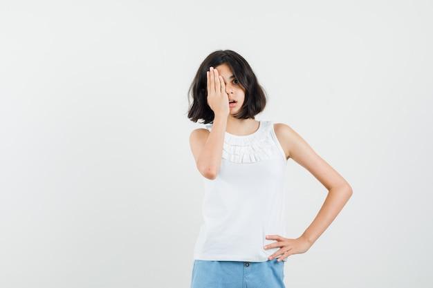 Bambina che tiene la mano sull'occhio in camicetta bianca, vista frontale di pantaloncini.