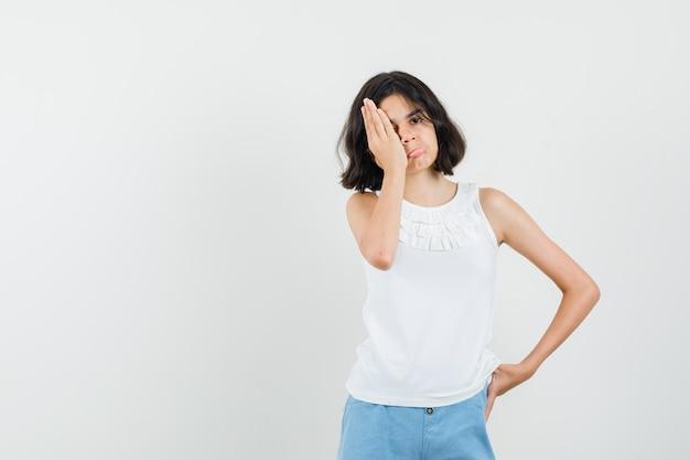 Bambina che tiene la mano sull'occhio in camicetta bianca, pantaloncini e sembra risentita. vista frontale.