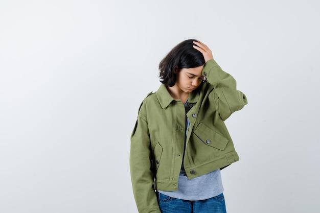 Bambina che tiene la mano sulla testa in cappotto, t-shirt, jeans e sembra smemorata. vista frontale.