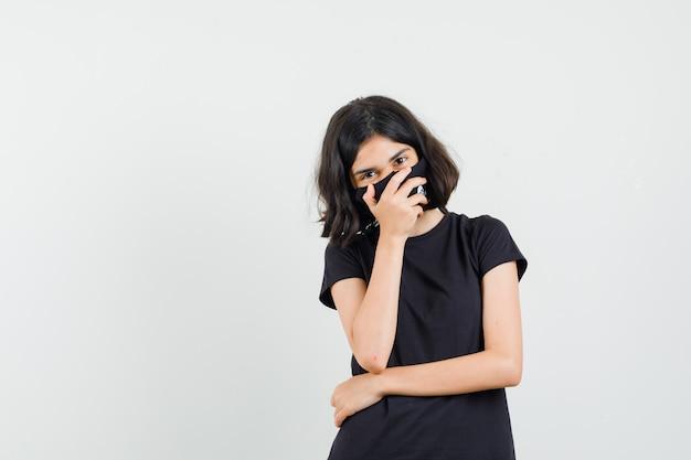 Bambina che tiene la mano sulla bocca in maglietta nera, maschera e che sembra felice, vista frontale.